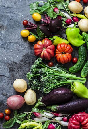 Frisches Gemüse der Saison, Lebensmittelhintergrund. Auberginen, Tomaten, Radieschen, Paprika, Brokkoli, Kartoffeln, Rüben auf dunklem Hintergrund, Draufsicht. Flach legen