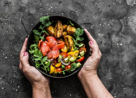 Smoked salmon, baked potatoes, fresh vegetables salad breakfast bowl in womens hands on a dark background, top view