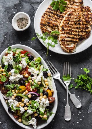 Mediterranean style lunch table - Greek chickpeas salad and pork chops on dark background, top view Imagens