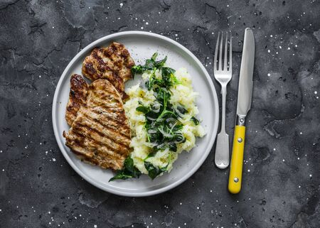 Turkey grilled chop and mashed potatoes with creamy spinach on a dark background, top view
