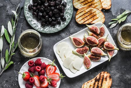 Mediterranean style snack appetizers - dried olives, figs, cheese, grilled bread, strawberries, raspberries and white wine on a dark background, top view