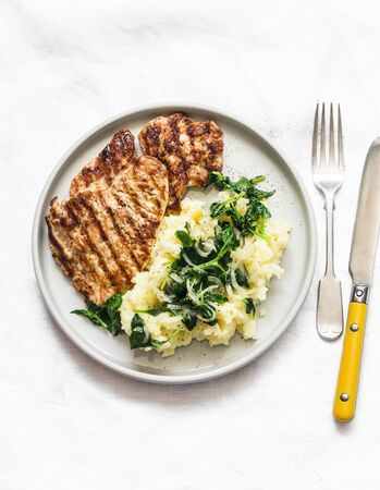 Turkey grilled chop and mashed potatoes with creamy spinach on a light background, top view