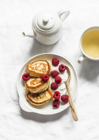 Sweet breakfast, snack, dessert - pancakes with sour cream and raspberries and green tea on a light background, top view