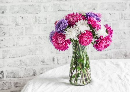 Bouquet purple aster flowers on the kitchen table on a light background. Cozy home concept Stockfoto