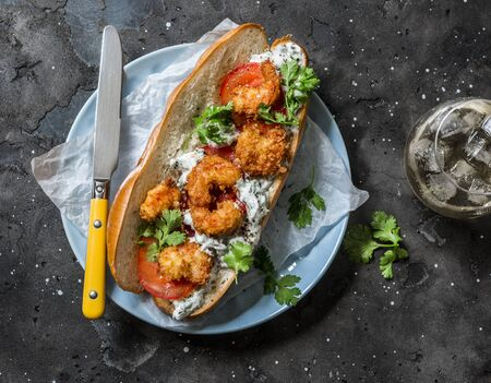 Fried crispy tempura shrimp, tomato and tzadziki sauce sandwich on dark background, top view