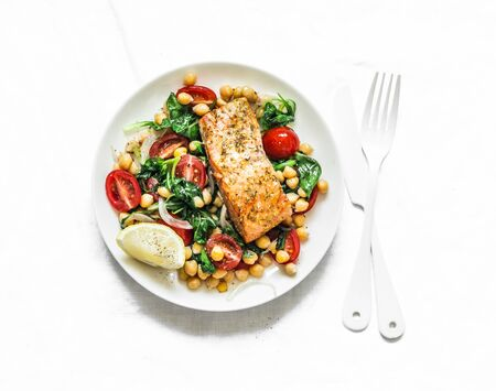 Warm chickpeas, cherry tomatoes, spinach salad and baked salmon - healthy lunch on a light background, top view Stockfoto