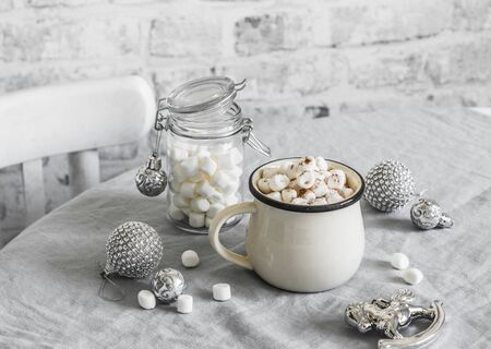 Hot chocolate with marshmallow - traditional Christmas winter warming drink on the bright kitchen table surrounded by Christmas decorations. Christmas mood inspiration