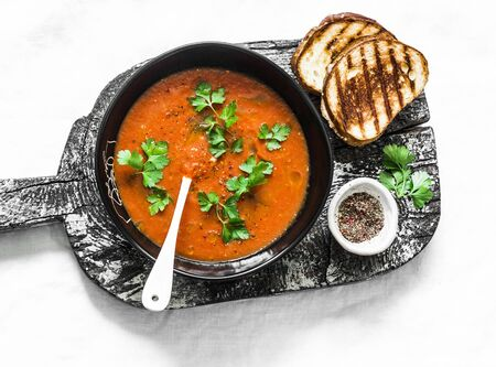 Baked tomato soup and grilled cheese hot sandwiches on light background, top view. Vegetarian food diet concept