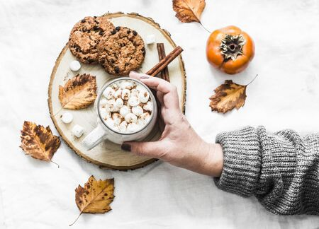 Womans hand in a warm sweater holds cup of hot chocolate. Cookies with chocolate chips and mug of hot chocolate on a light background, top view. Cozy autumn winter still life
