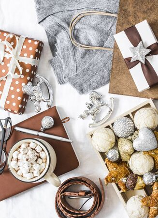 Christmas mood background. Festive Christmas shopping concept. Grey cashmere pullover, gift box, notepad, christmas decorations, hot chocolate with marshmallow on white background, top view. Flat lay