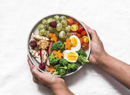 Female hands holding a large snack plate. Boiled egg, broccoli, carrots, apples with peanut butter, grapes - delicious diet breakfast, snack on a light background, top view Standard-Bild