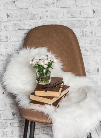 Brown soft loft style chair, fur rug, stack of books, bunch of chrysanthemums on light wall background. Interior concept, copy space 스톡 콘텐츠