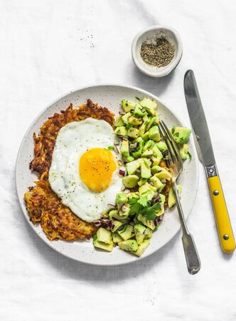 Sweet potato rostis with fried egg and avocado salsa on light background, top view Zdjęcie Seryjne