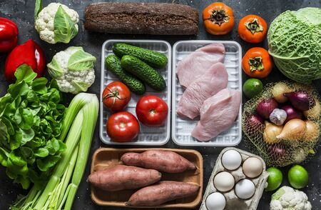 Fresh organic vegetables, fruits, turkey meat, eggs, whole wheat bread on a dark background, top view. Healthy diet food concept. Menu planning
