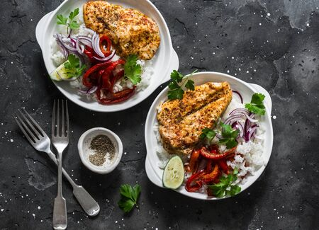 Baked spicy chicken with sweet pepper and rice - delicious mexican style lunch on a dark background, top view. Fajitas bowl