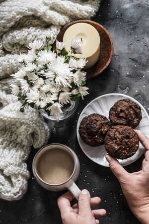Women's hands hold chocolate cake and mug of coffee on a dark table with cozy knitted scarf, bouquet of white chrysanthemums and a candle in a wooden bowl. Cozy home Standard-Bild - 134138863
