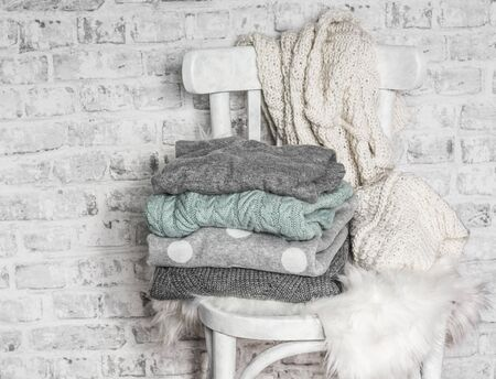 Stack of cozy winter autumn sweaters on an old white wooden chair in a light room Standard-Bild - 134138869