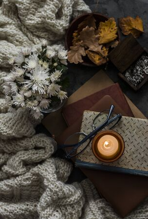 Stack of books, candle, autumn leaves, knitted plaid - cozy home still life on a dark background, top view Standard-Bild - 134138870