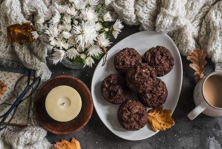 Chocolate cakes with almonds, coffee, knitted plaid, book, bouquet of chrysanthemums, candle on a dark background, top view Standard-Bild - 134138871