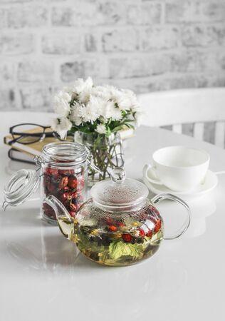 Currant, raspberry leaves, rose hips herbal tea in glass teapot on kitchen table. Rising immunity. Home cozy still life Standard-Bild - 134138873