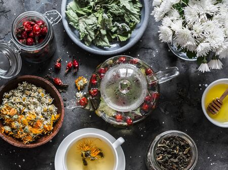 Herbal tea with currant, mint, raspberry leaves, chamomile and calendula flowers, rose hips, teapot on a dark background, top view. Flat lay Standard-Bild - 134138882