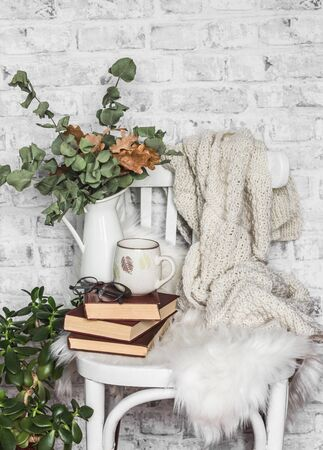Concept of a cozy home. Old chair, stack of books, cup, knitted plaid, dry eucalyptus's branches on the background of a light wall Standard-Bild - 134138875