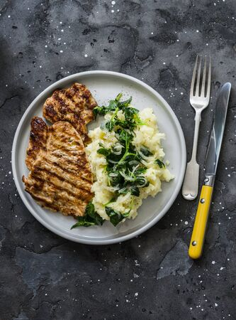 Turkey grilled chop and mashed potatoes with butter spinach on a dark background, top view. Comfort winter autumn home cooked food Standard-Bild - 134139859