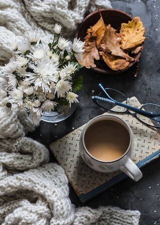 Coffee break. Coffee mug, book, cozy plaid, autumn leaves on dark background, top view Standard-Bild - 134140058