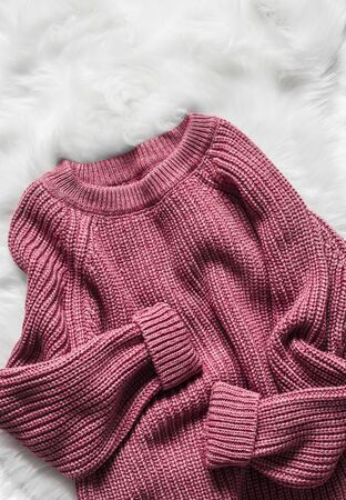 Color raspberry woolen women's sweater on a white fluffy carpet, top view. Fashion concept Standard-Bild - 134140066