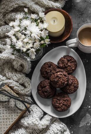 Chocolate cakes with almonds, coffee, knitted plaid, book, bouquet of chrysanthemums, candle on a dark background, top view Standard-Bild - 134140093