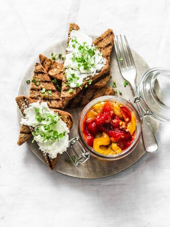 Marinated roasted grilled bell pepper, cream cheese bruschetta - delicious snack, appetizers, tapas on a light background, top view