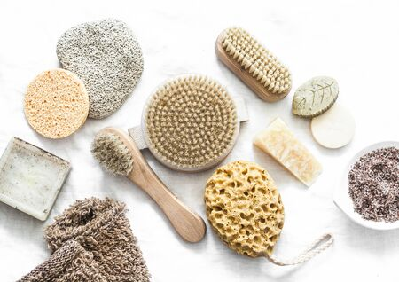 Body skin care. Brushes with natural bristles, pumice, homemade soap, scrub on a light background, top view