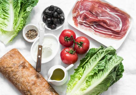 Ingredients for bruschetta - prosciutto, ciabatta bread, romano salad, olives, tomatoes, cream cheese on a light background, top view. Flat lay