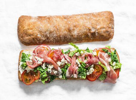 Bruschetta with prosciutto, ciabatta bread, romano salad, tomatoes, cream cheese on a light  background, top view Stok Fotoğraf