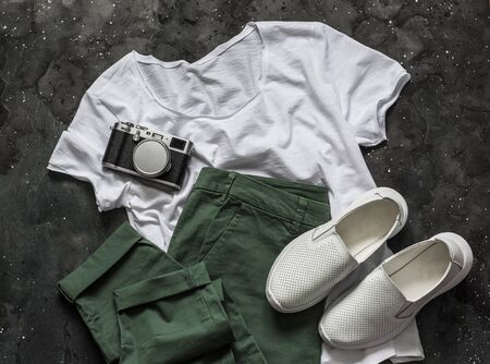 Womens clothing for summer spring walks - cotton green trousers, a basic white t-shirt, white sneakers and a vintage camera on a dark background, top view. Fashion concept