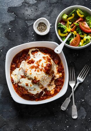 Turkey tomato sauce mozzarella cheese meatloaf and fresh tomato yellow bell pepper vegetables salad on a dark background, top view. Healthy balanced diet food