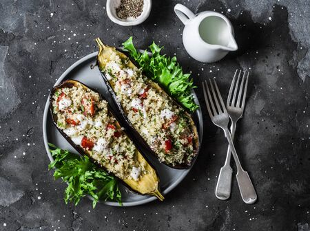 Grilled eggplant stuffed with couscous, tomatoes, cilantro with yogurt sauce on a dark background, top view Stock Photo