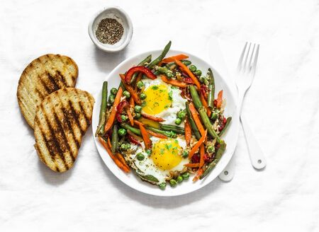 Eggs vegetable stir fry asian style shakshuka on a light background, top view. Delicious healthy breakfast, lunch