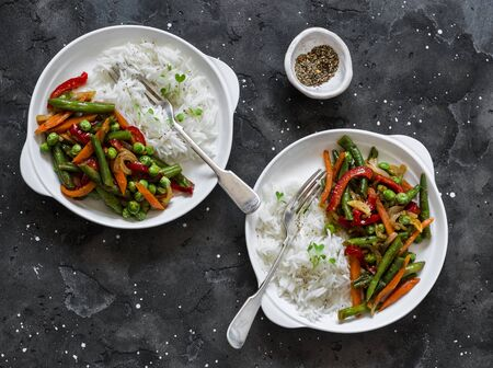 Green beans, sweet peppers, carrots, onions, green peas stir fry and rice on a dark background, top view. Fast diet vegetarian lunch