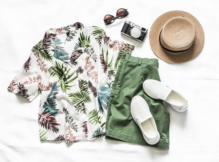 Set of women's clothing for vacation, travel - shirt, cotton shorts, leather sneakers, hat, sunglasses and camera on a light background, top view Imagens