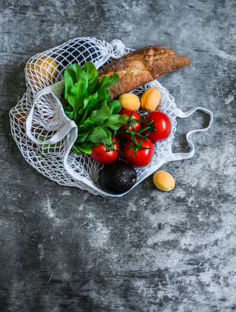 Fresh baguette bread, organic tomatoes, apricots, spinach, avocado, kiwi in a textile eco bag on a gray background, top view. Grocery planning  concept Banque d'images