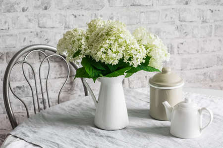 Cozy kitchen in scandinavian style. Bouquet of hydrangeas, teapot, metal jar on the table in a bright room. Cozy home concept