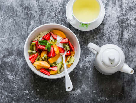 Cottage cheese with natural yogurt and fresh fruit strawberries, kiwi, apricots, and green tea on a gray background, top view Reklamní fotografie