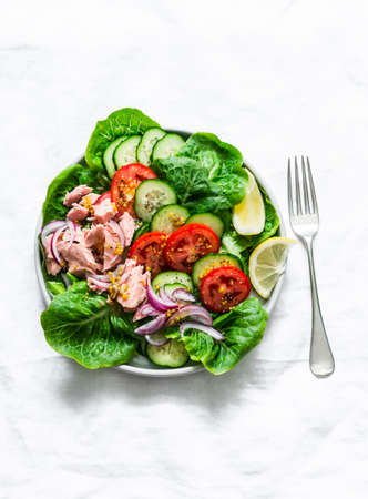 Healthy balanced food - canned tuna, tomatoes, cucumbers, lettuce, red onion, olive oil salad for appetizer, lunch, tapas on a light background, top view