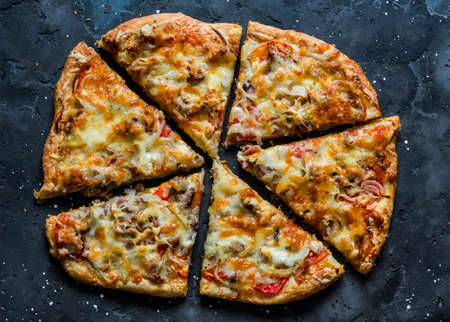 Canned tuna, tomatoes, mozzarella cheese puff pastry pizza on a dark background, top view