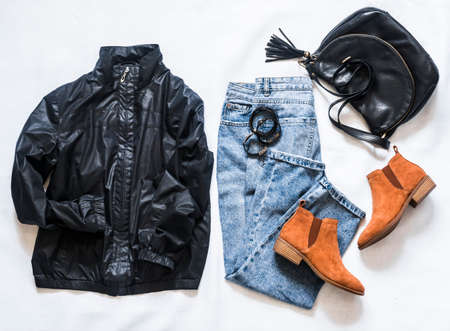Women's clothing black jacket windbreaker, mom's blue jeans, black leather bag, brown suede chelsea shoes on a light background, top view. Flat lay fashion concept