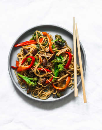 Mushrooms, broccoli, sweet peppers, teriyaki stir fry sauce with noodles on a light background, top view Standard-Bild