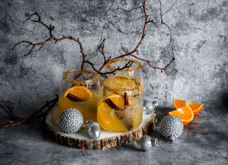 Christmas alcohol orange cocktail on a gray background. Christmas still life
