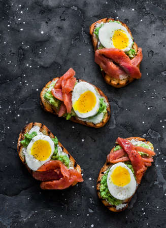 Cream cheese, avocado, red salted fish, boiled egg sandwiches on a dark background, top view Stockfoto