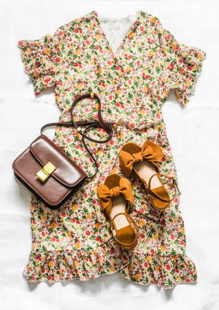 Floral print dress, suede wedge shoes and cross body bag - women's summer clothing on a light background, top view